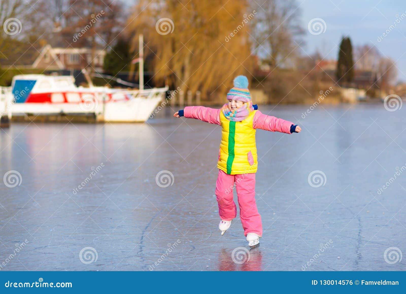 Patinaje de hielo del niño en el canal congelado del molino en Holanda
