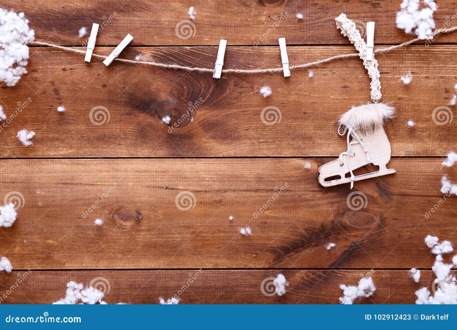 Patinando no conceito do inverno, patim de gelo branco que pendura no fundo marrom de madeira com flocos de neve, vista superior