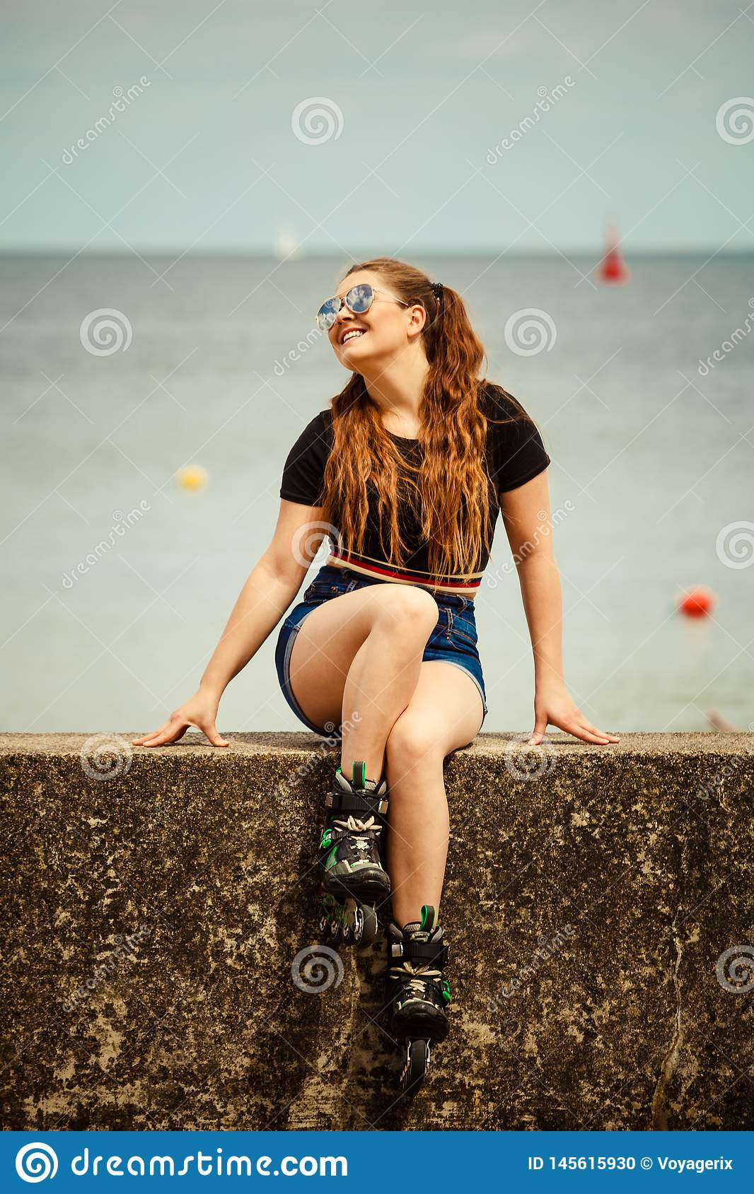 Patins de rolo vestindo da jovem mulher feliz