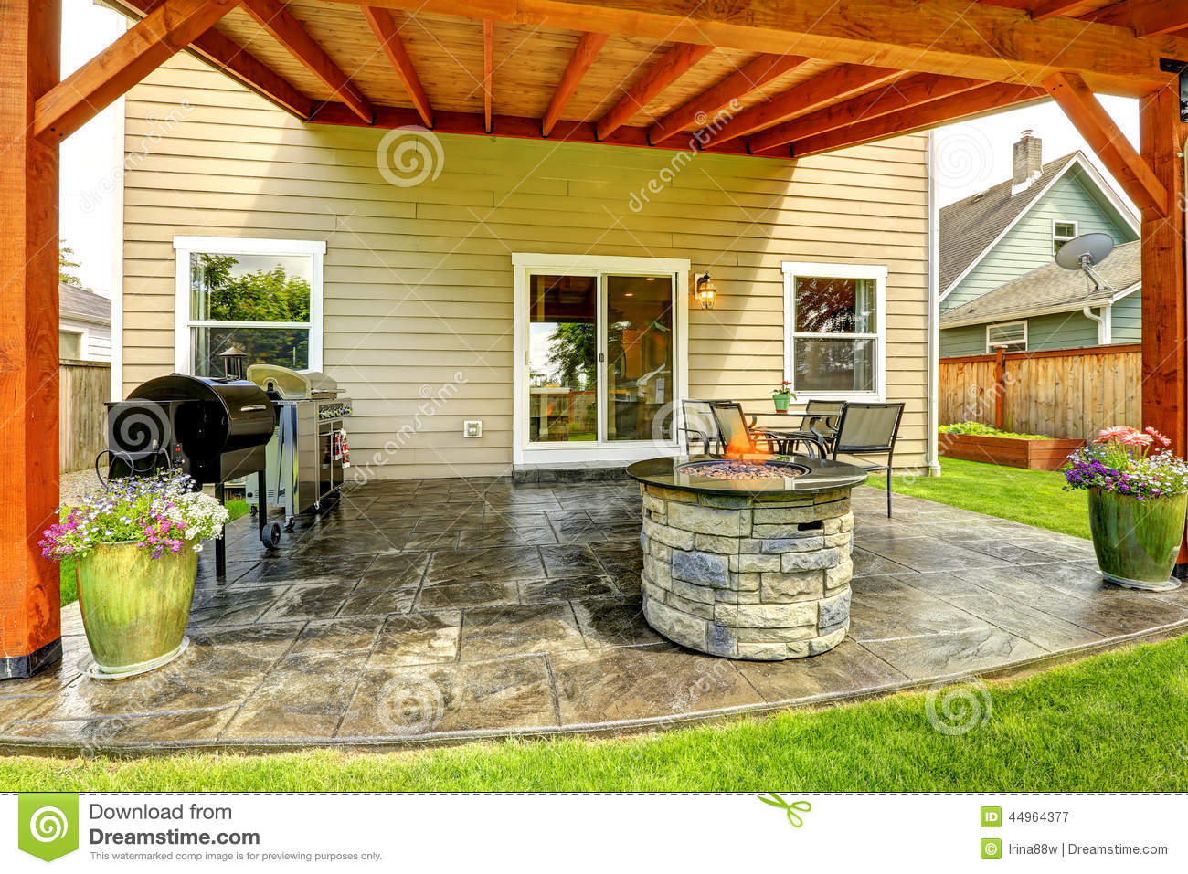 Pergola with patio area. Tile floor decorated with flower pots. Stone ...