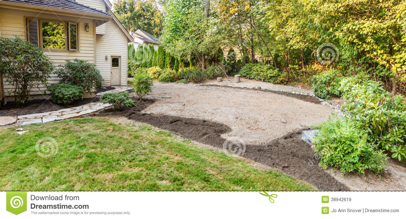 ... flower bed areas and stone retaining wall built around the far edge