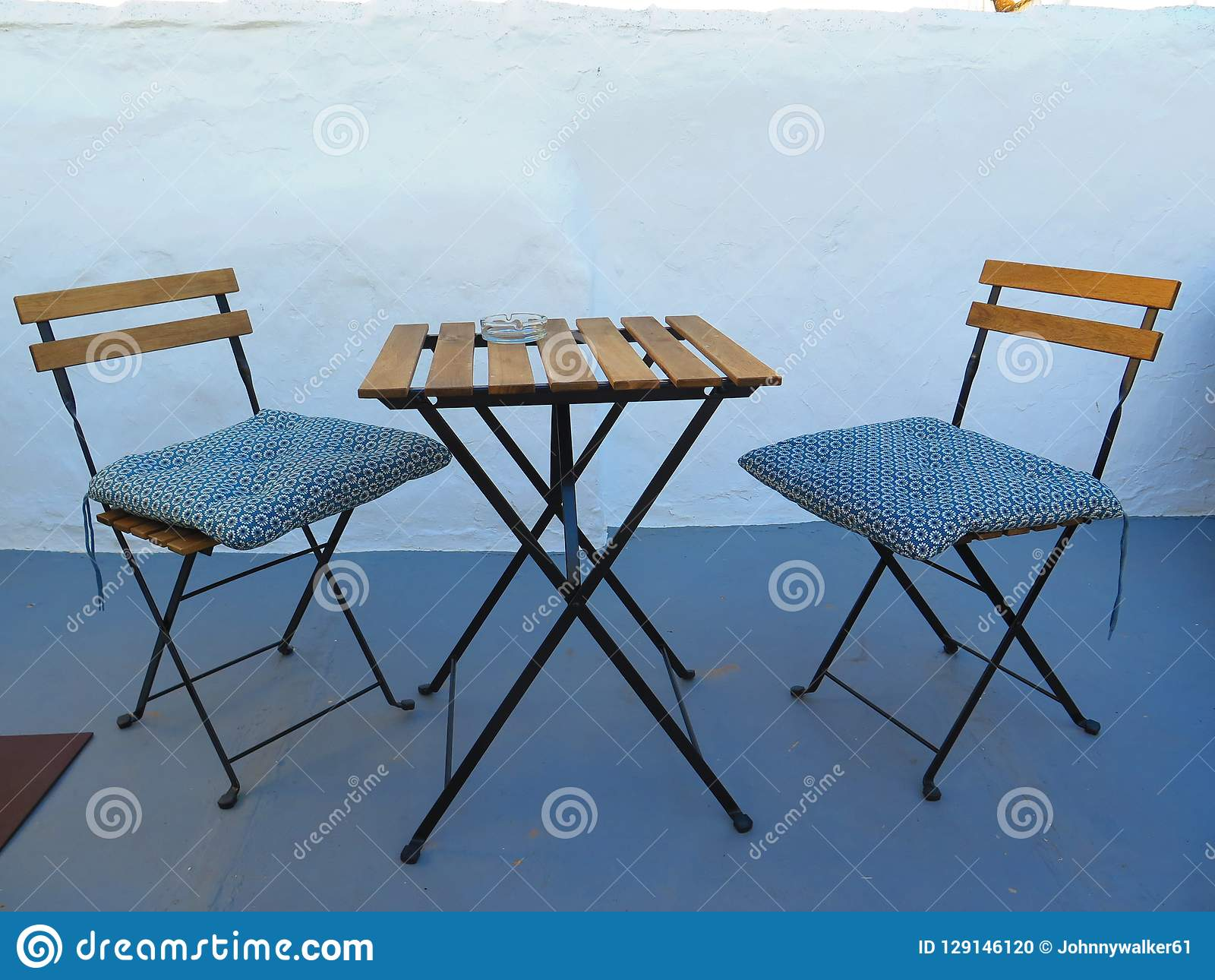 Two spindly chairs with cushions and small square table in andalusian courtyard patio