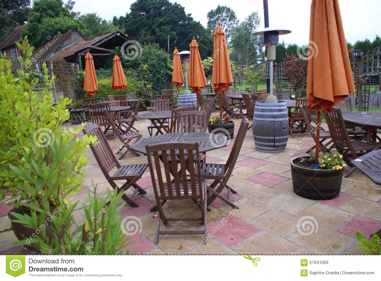 Patio Furniture Of Umbrellas, Wooden Chairs, And Wooden Tables