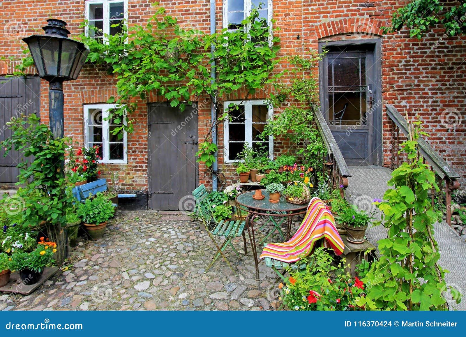 Patio hermoso de la casa vieja con las flores, ciudad real Ribe, Dinamarca