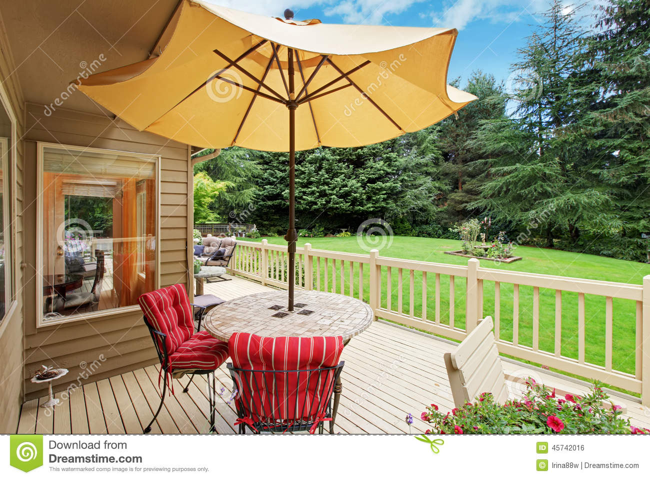 patio table with yellow umbrella on walkout deck stock photo