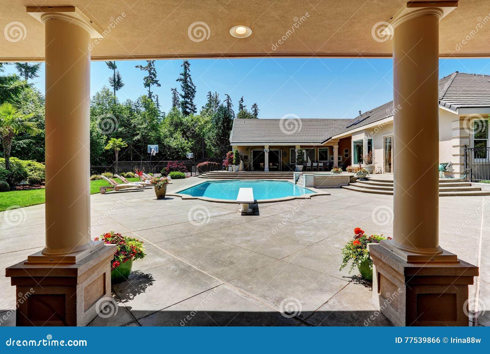 Patio trasero moderno con la piscina en la mansi n for Patios modernos con piscina