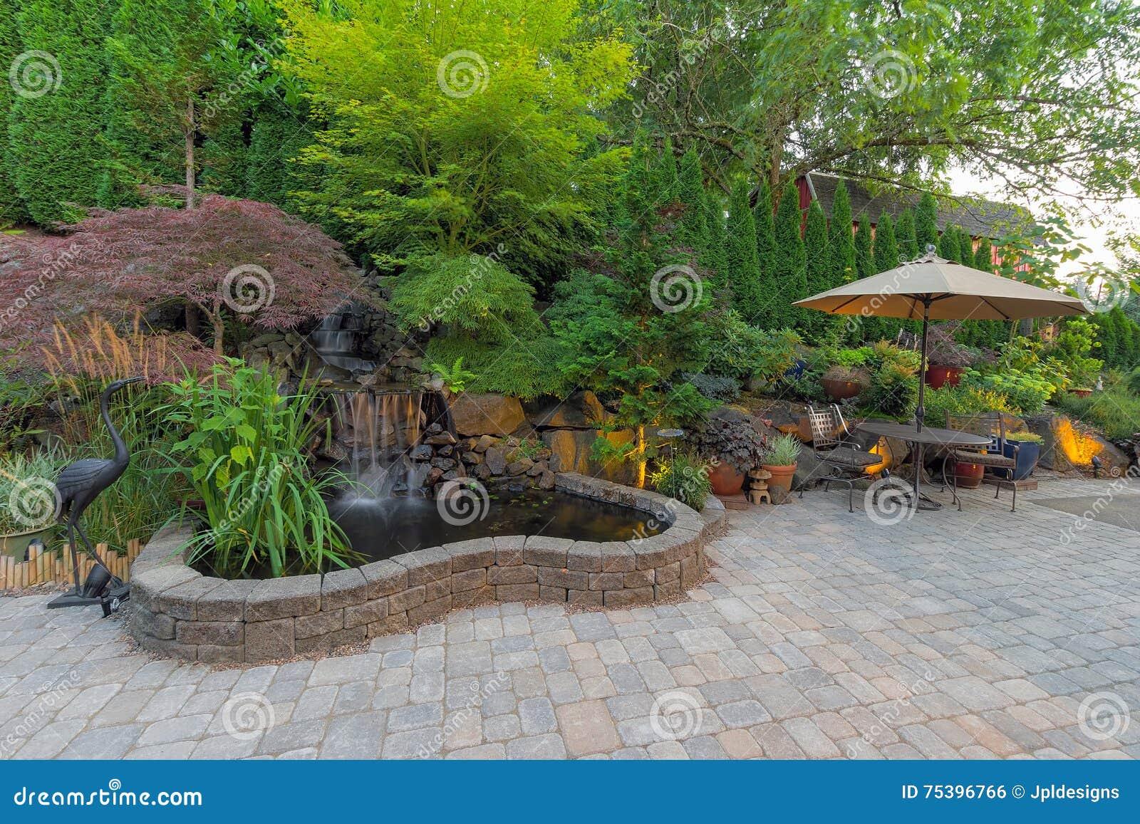 Patio trasero que ajardina el patio con la charca de la cascada