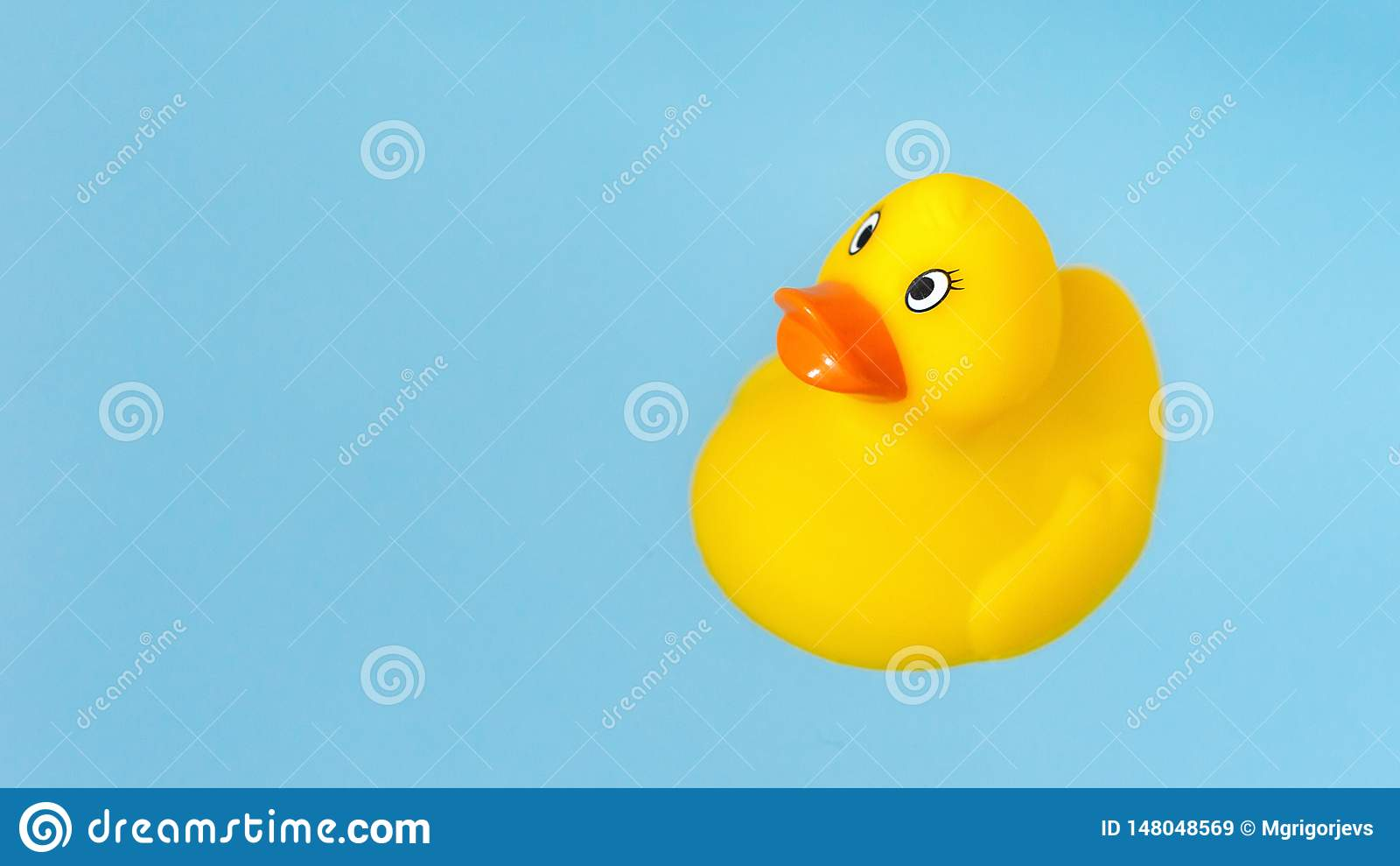 Pato de goma amarillo del baño en agua azul