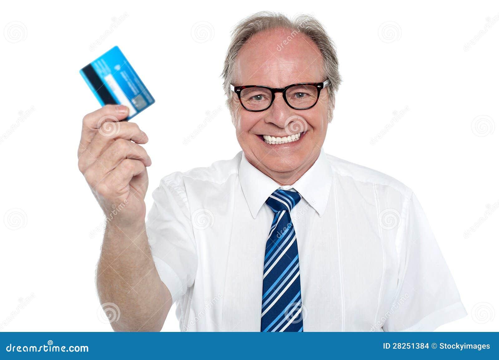 Patrón envejecido alegre que soporta una tarjeta de débito