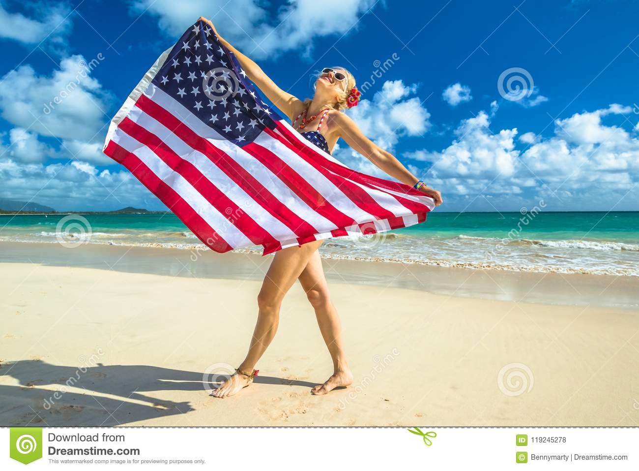 1e72f374daea3 Smiling woman with american flag bikini waving american flag in spectacular  tropical Lanikai Beach, east shore of Oahu in Hawaii, USA.