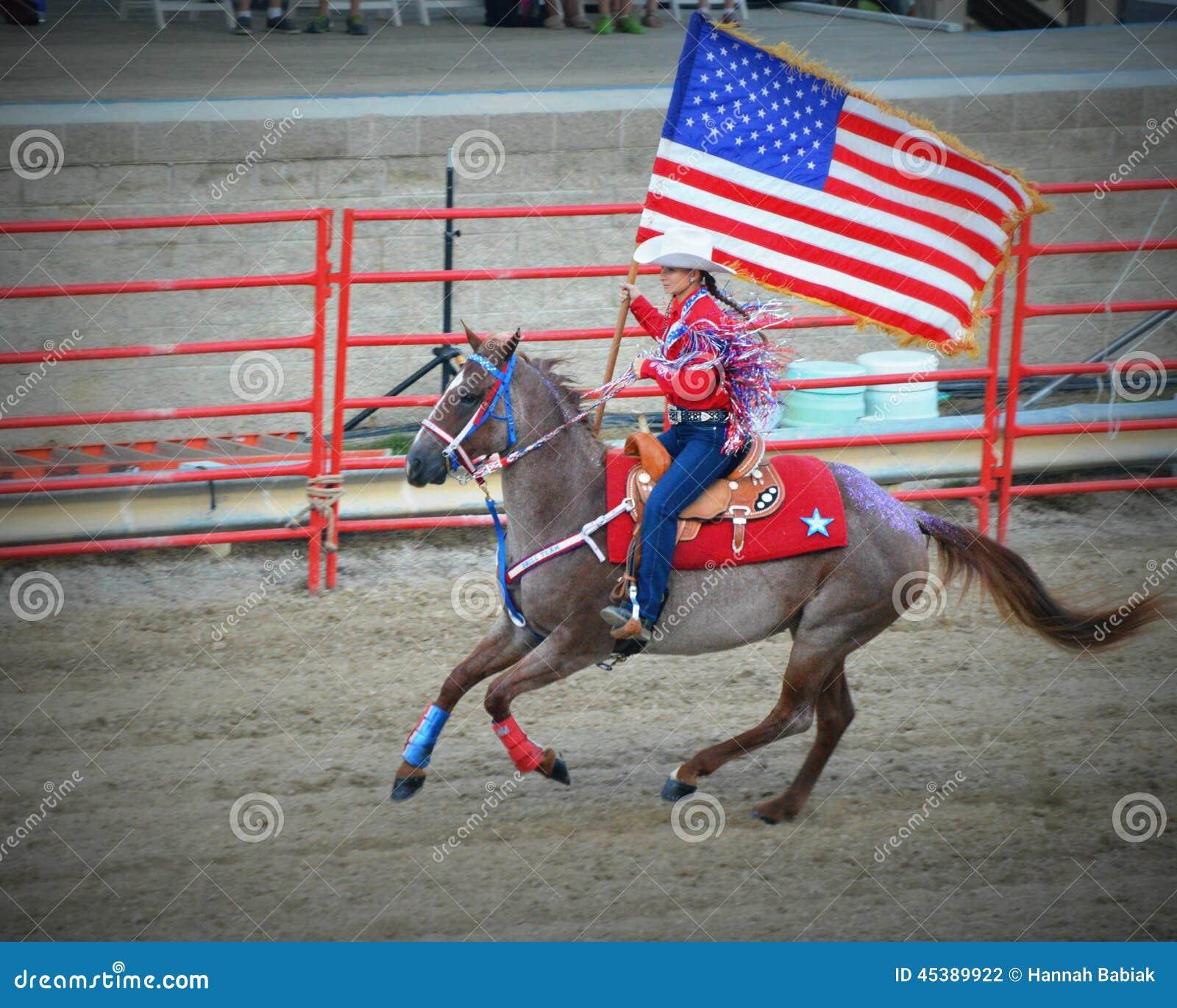 Patriotisk cowgirl på hästrygg med flaggan