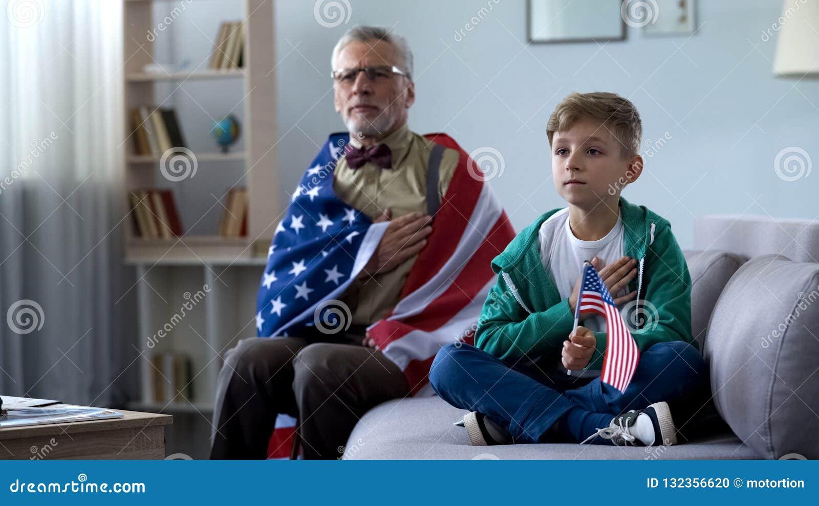 Patriotisk gamal maninnehavamerikanska flaggan, lyssnande nationalsången med sonsonen