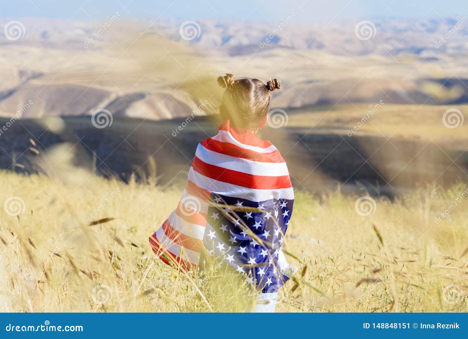 Patriottische vakantie Gelukkig leuk jong geitje, weinig kindmeisje met Amerikaanse vlag De V.S. vieren 4 van Juli