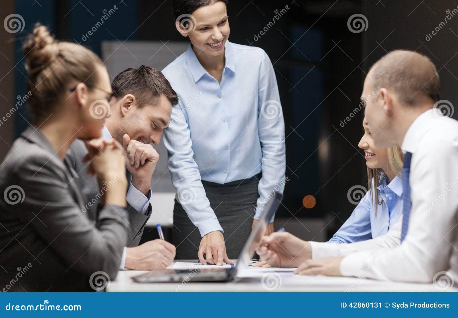 Patron féminin de sourire parlant à l équipe d affaires