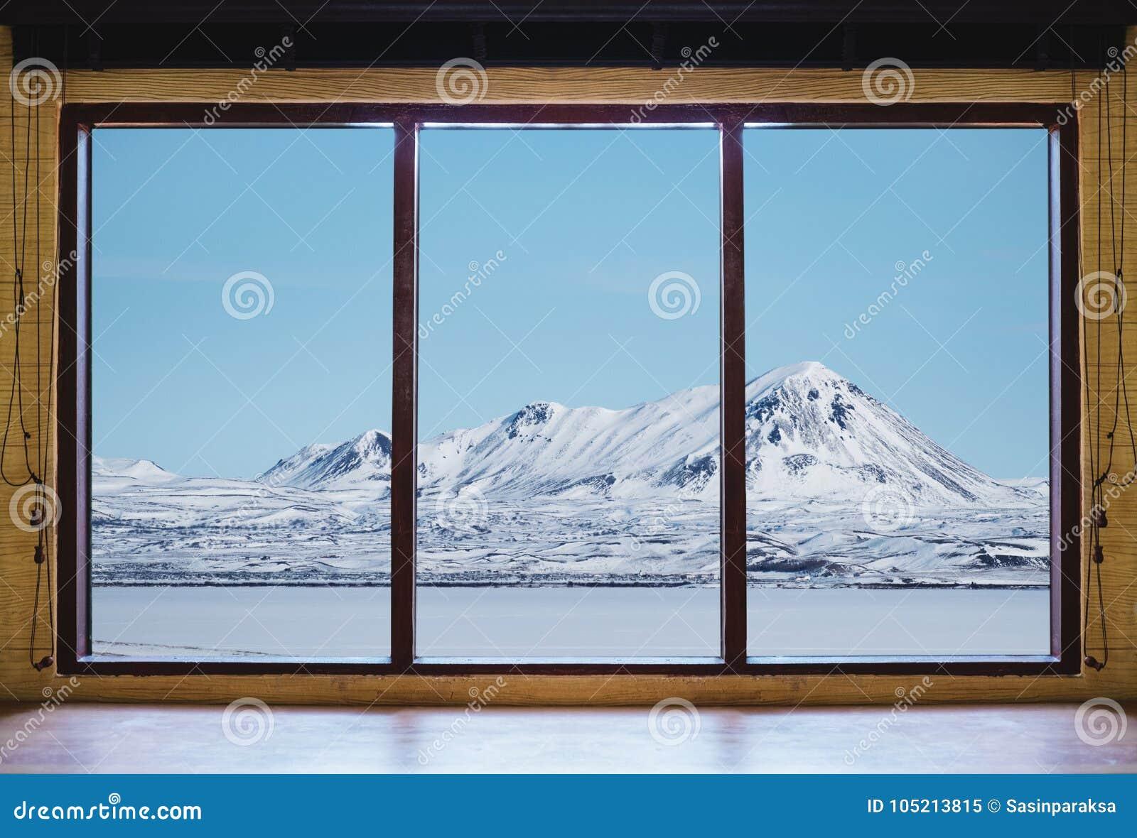 Patrzejący przez okno w zimie, drewnianej nadokiennej ramy z śnieżną górą i zamarzniętego jeziornego widoku w Iceland, biurka i k