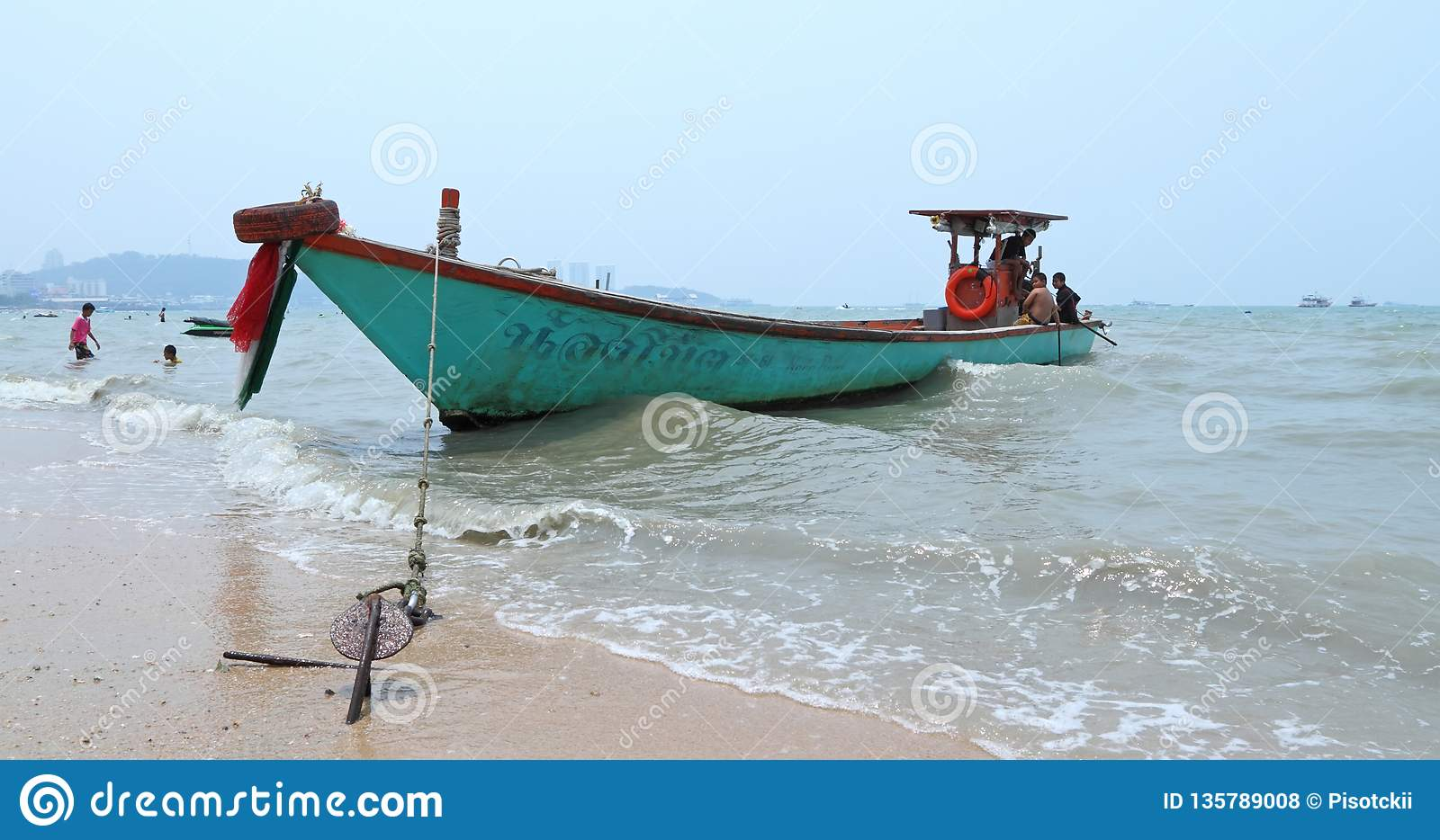 Motor boat near the shore among the waves on the coast of Pattaya in the Kingdom of Thailand