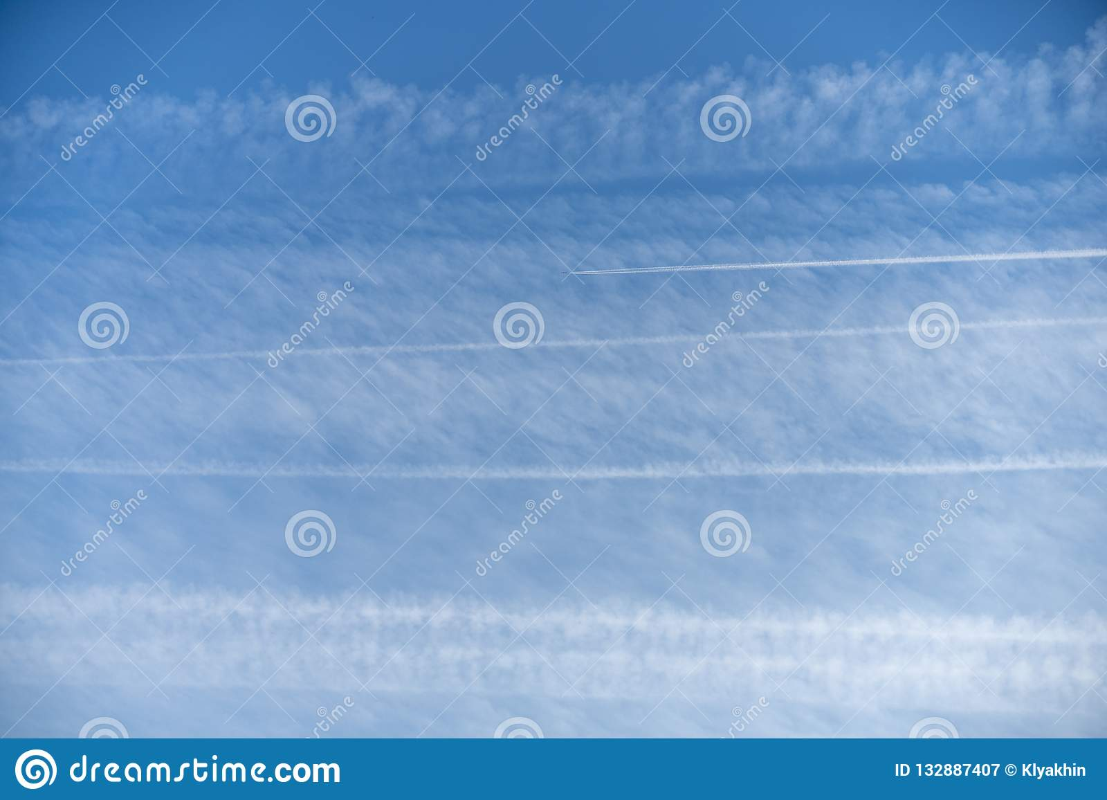 Pattern of airplane trails of condensed air crisscrossing each other against the blue sky