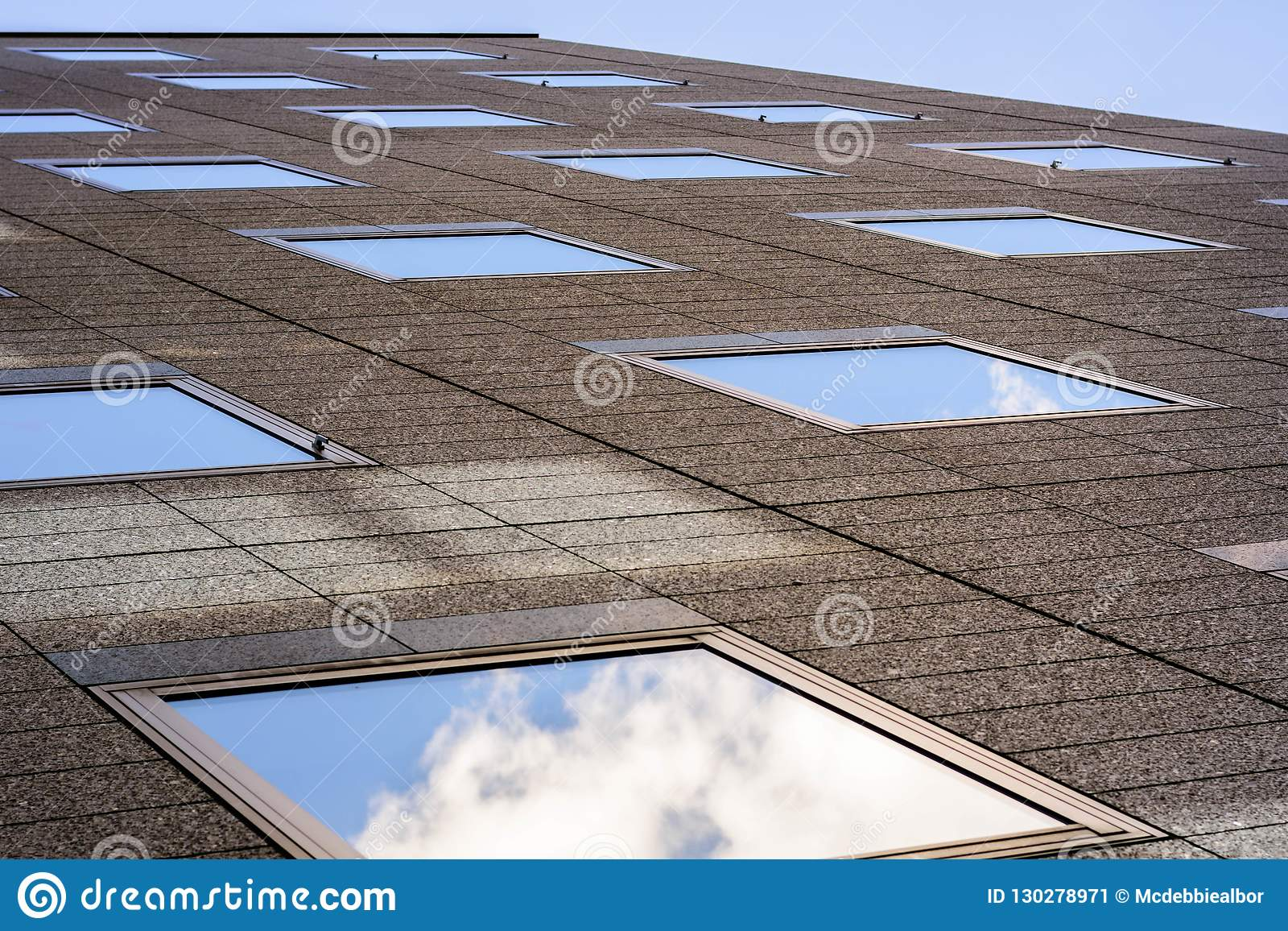 Brown office building exterior with square mirror patterns reflecting the sky and the clouds shot from the bottom.