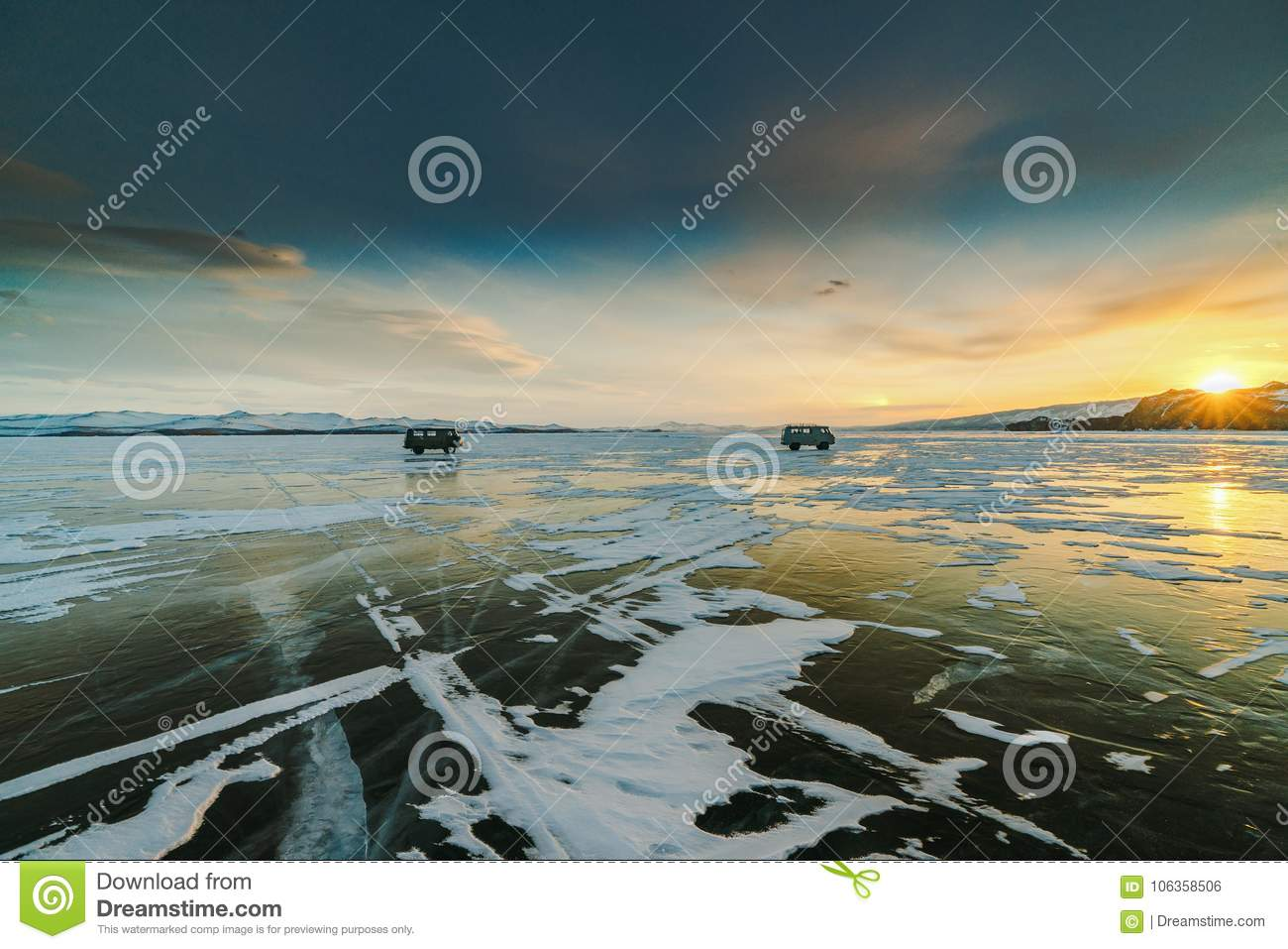 Pattern on ice of lake Baikal during sunset with two cars. Siberia Russia