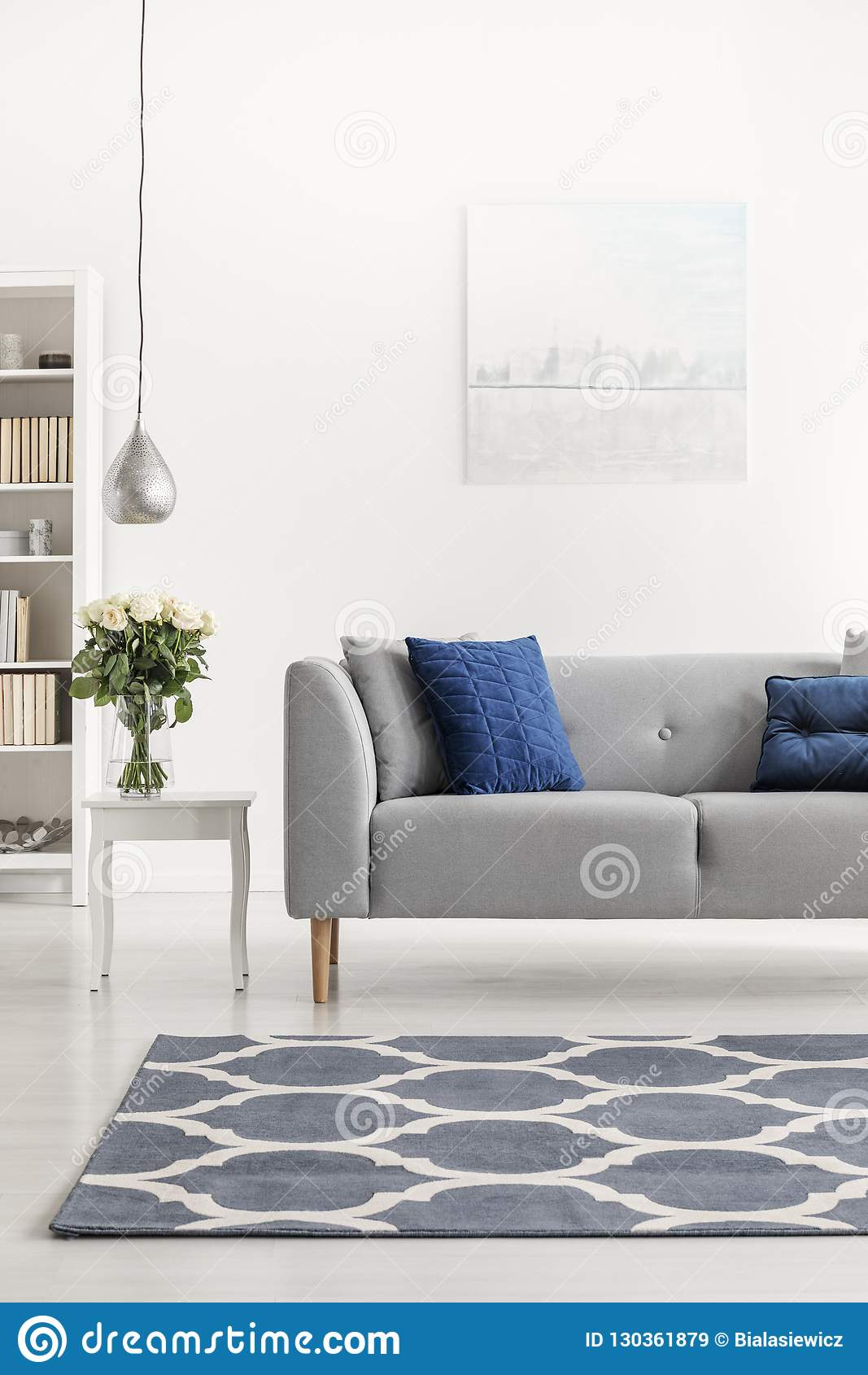 Patterned Carpet In Front Of Grey Couch With Blue Pillows In
