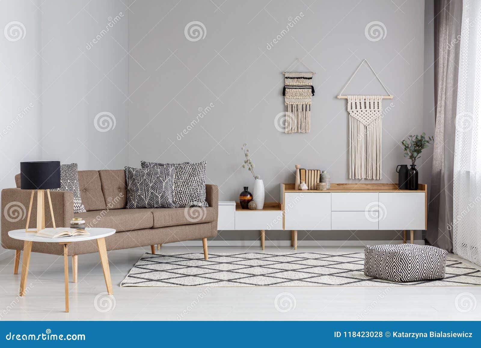 Patterned pouf on carpet near brown sofa in modern living room i