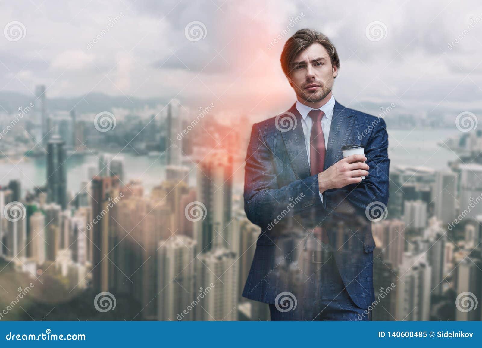 Pausa caffè di Enjoing Ritratto della tazza di caffè sicura e attracrive della tenuta dell uomo d affari mentre stando contro di