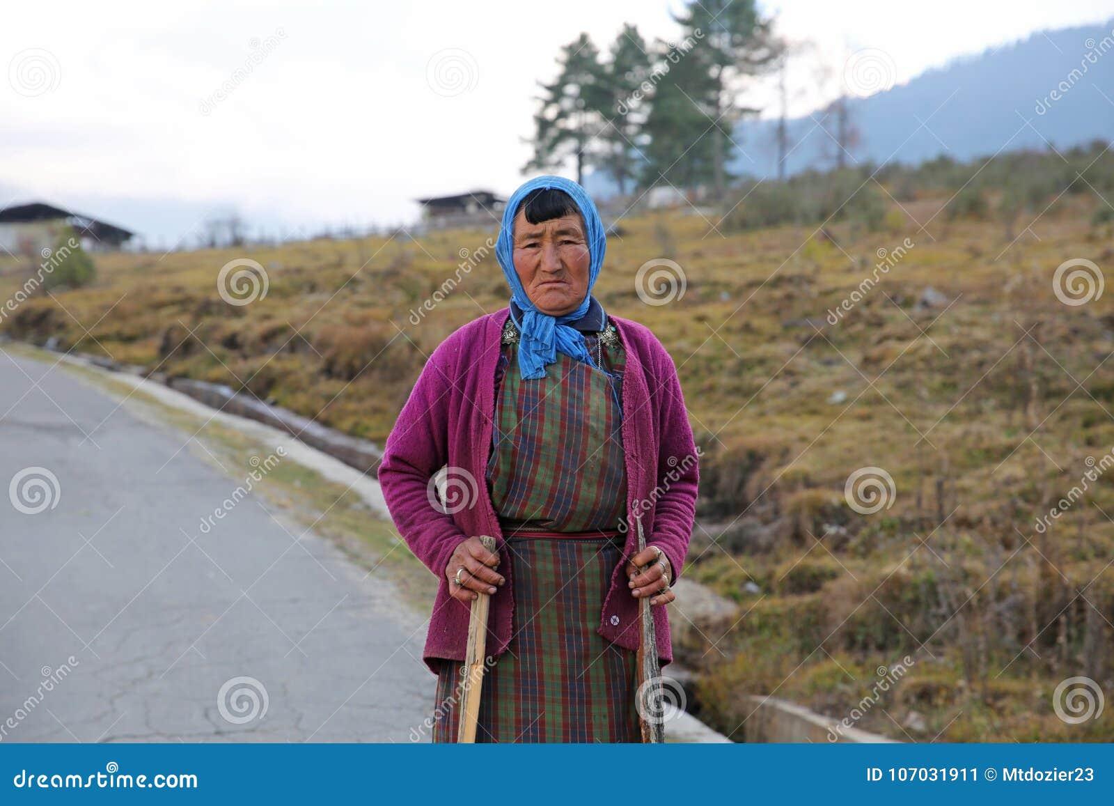 Pausas coloridas de la mujer de ella trabajo en Bhután rural