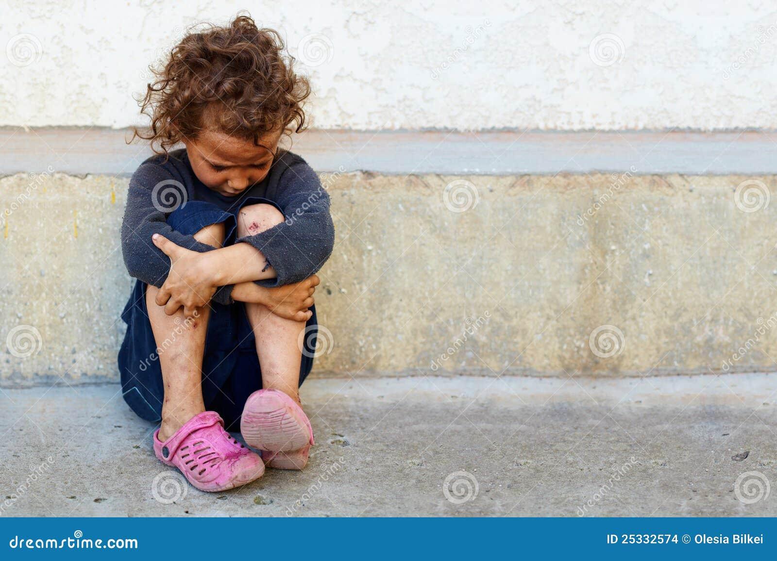 Pauvres, petit enfant triste contre le mur en béton