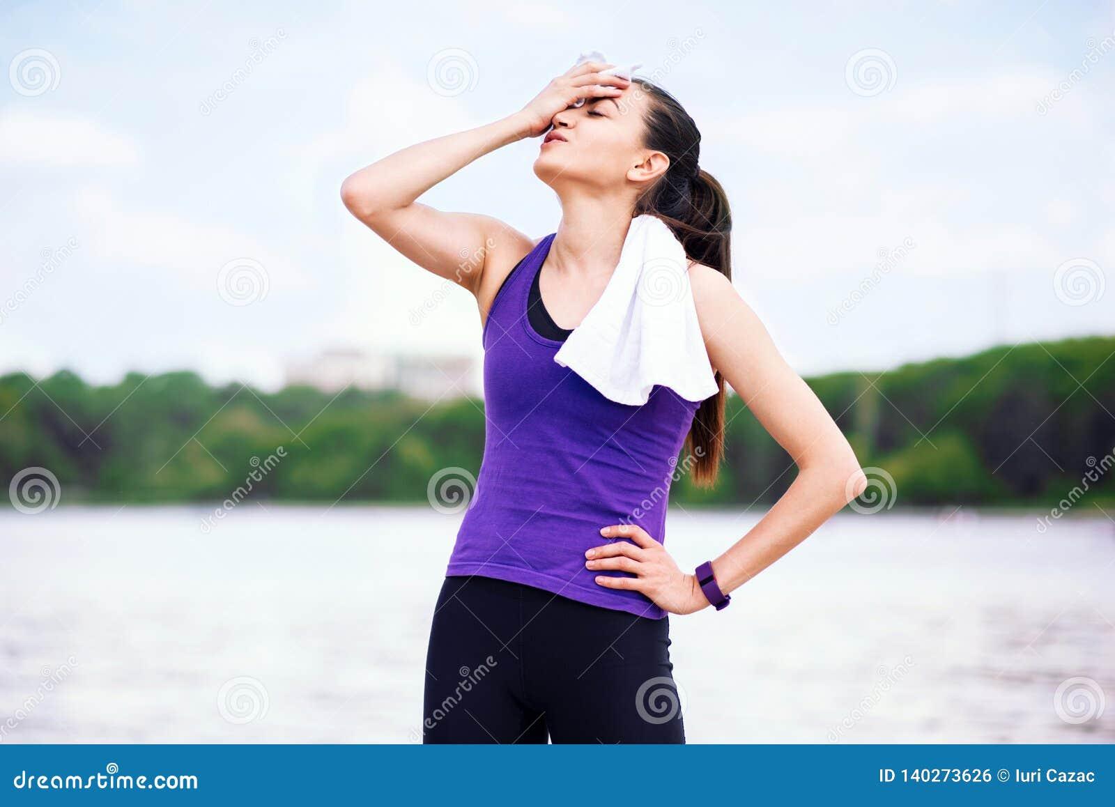 Pauze en recreatie vóór of na training en het lopen in park Aantrekkelijke vrouw op purpere t-shirt, op aardachtergrond