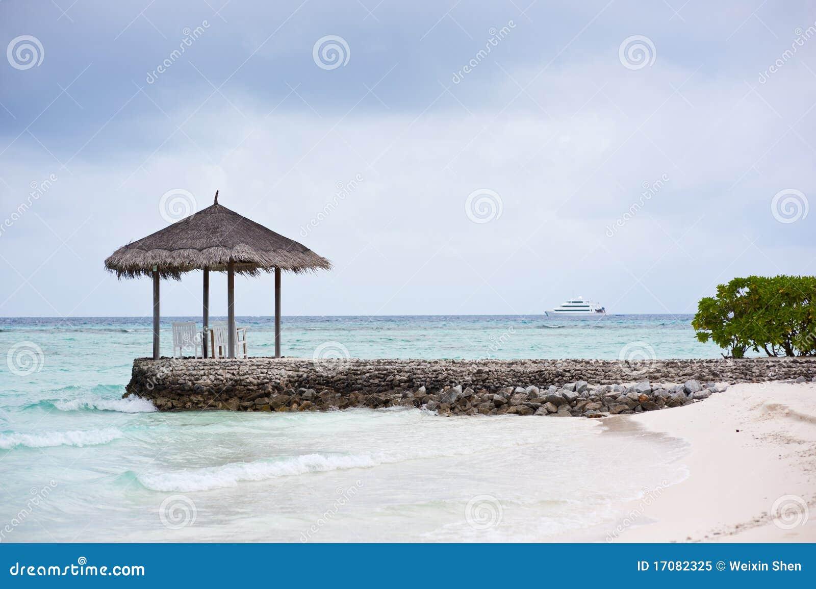 Pavilhão Thatched na praia em maldives