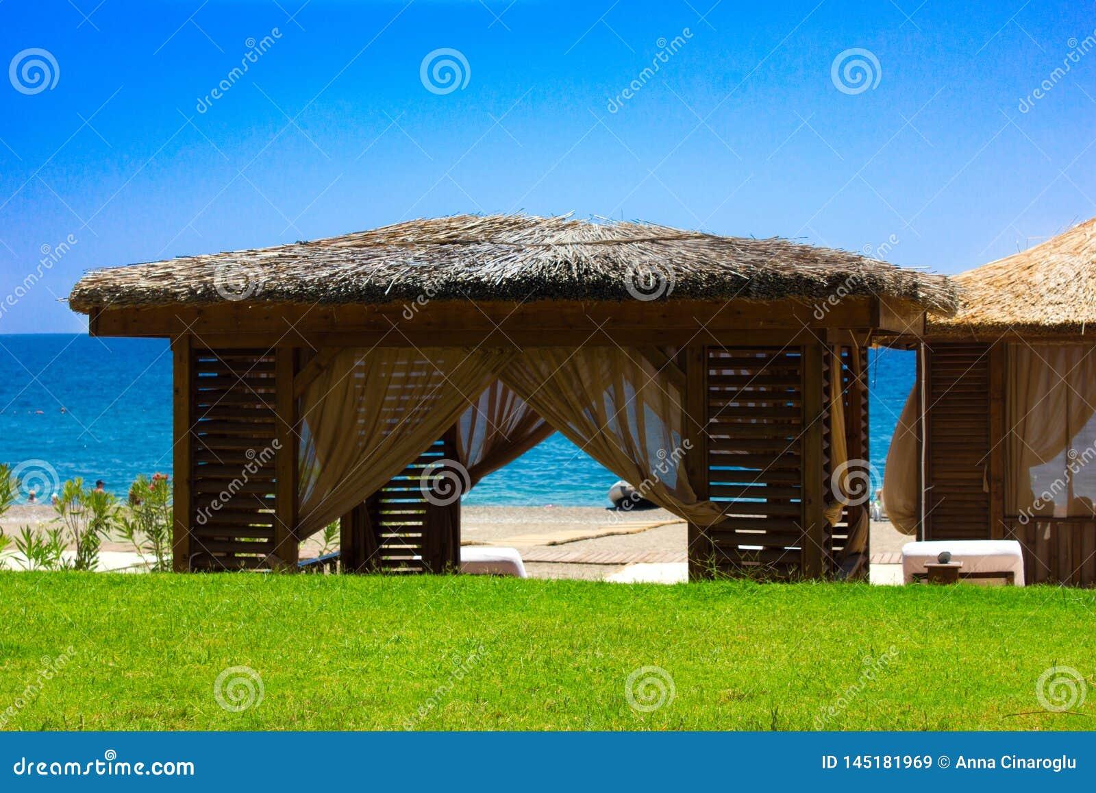 Paviljong med ett halmtäckt tak på en sandig strand Medelhavs- sommar och hav