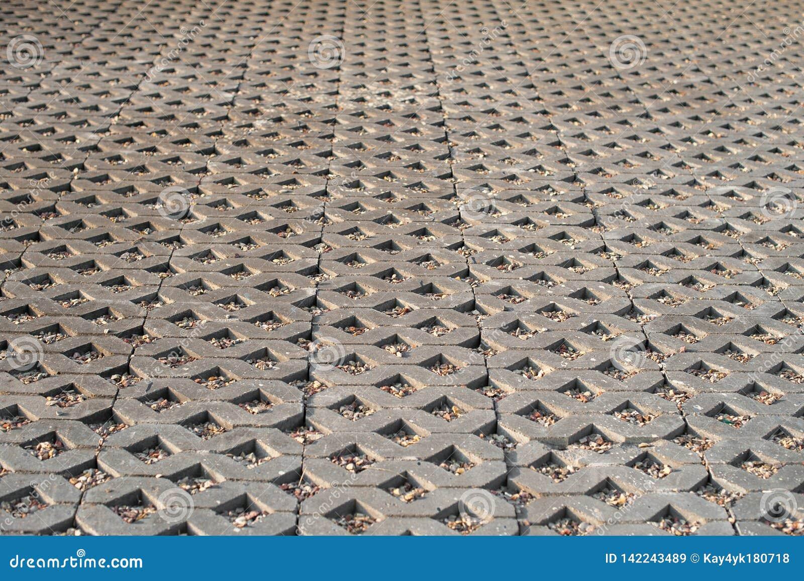 Pavimentazione delle mattonelle grige in un rombo, sabbia nelle mattonelle sotto forma di triangolo, la struttura delle mattonell