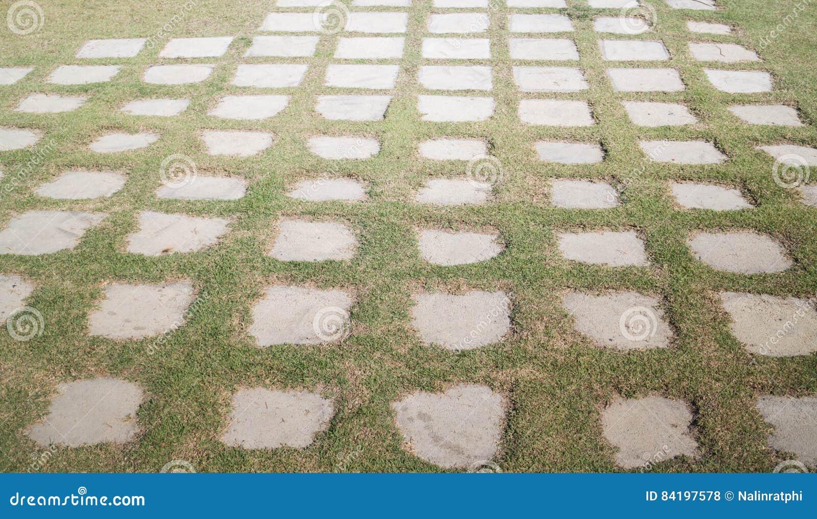 Pavimento di calcestruzzo con erba verde fotografia stock