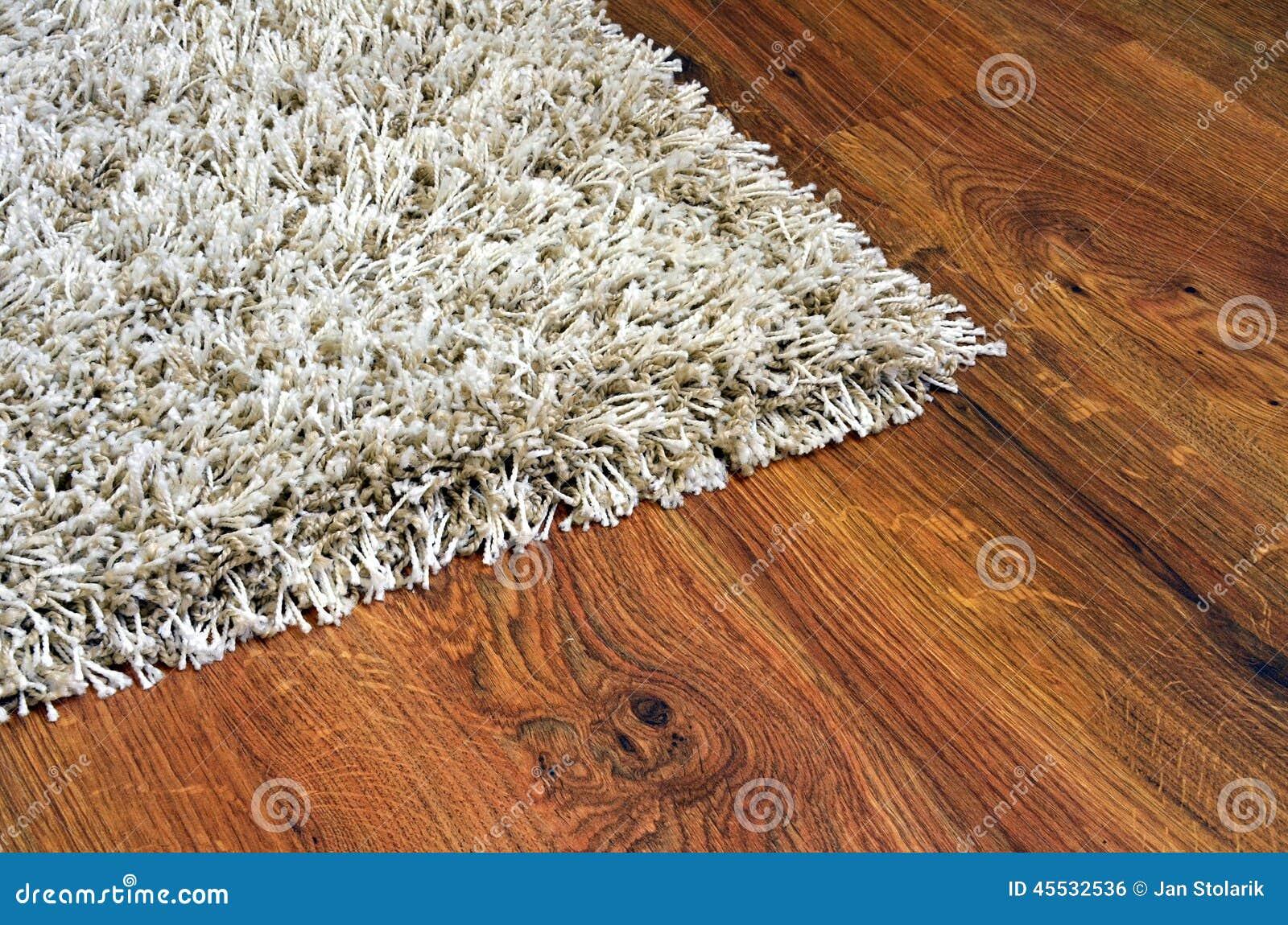 Pavimento di parquet delle plance di legno e del tappeto bianco