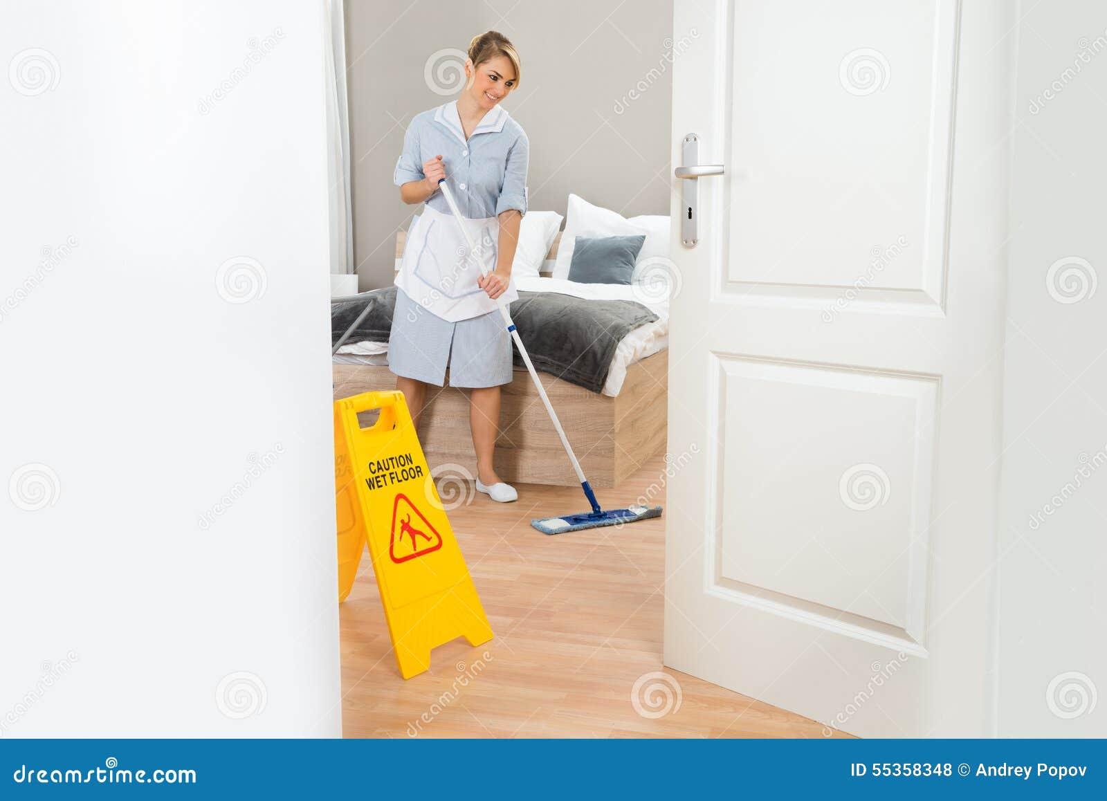 Pavimento di pulizia della domestica con la zazzera