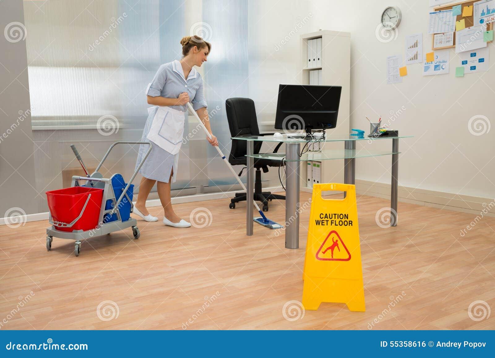 Pavimento di pulizia della domestica in ufficio