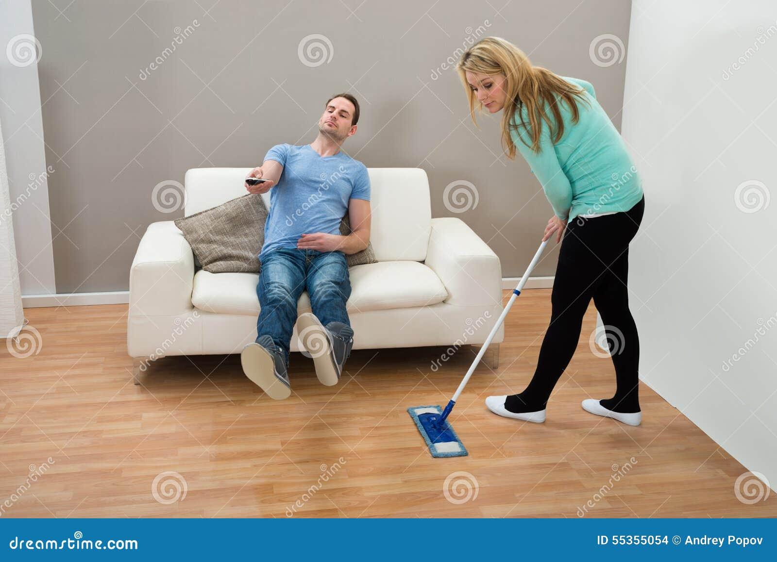 Pavimento di pulizia della donna mentre uomo sul sofà