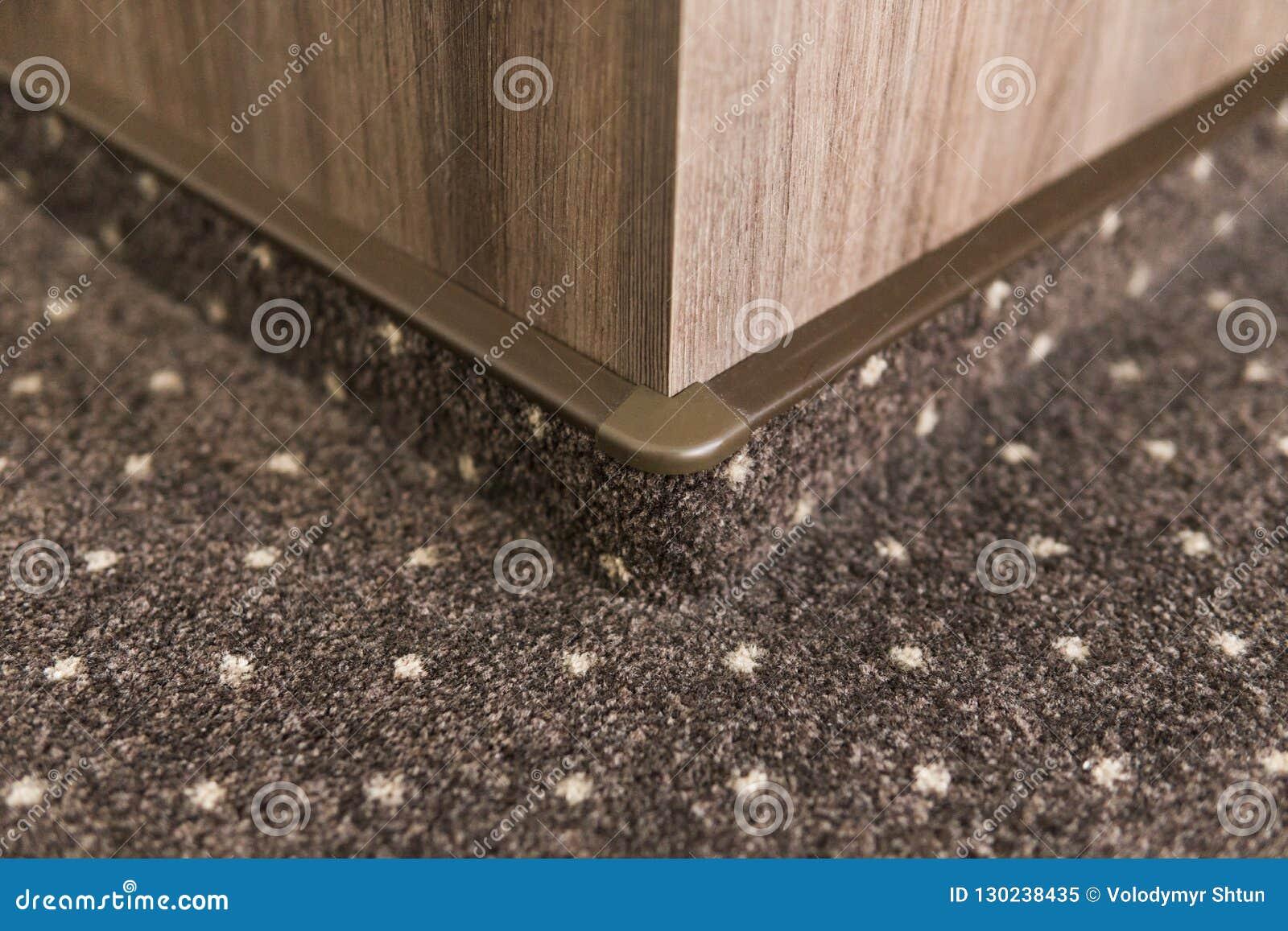 Battiscopa Staccato Dal Pavimento pavimento di tappeto di brown con punti bianchi con una
