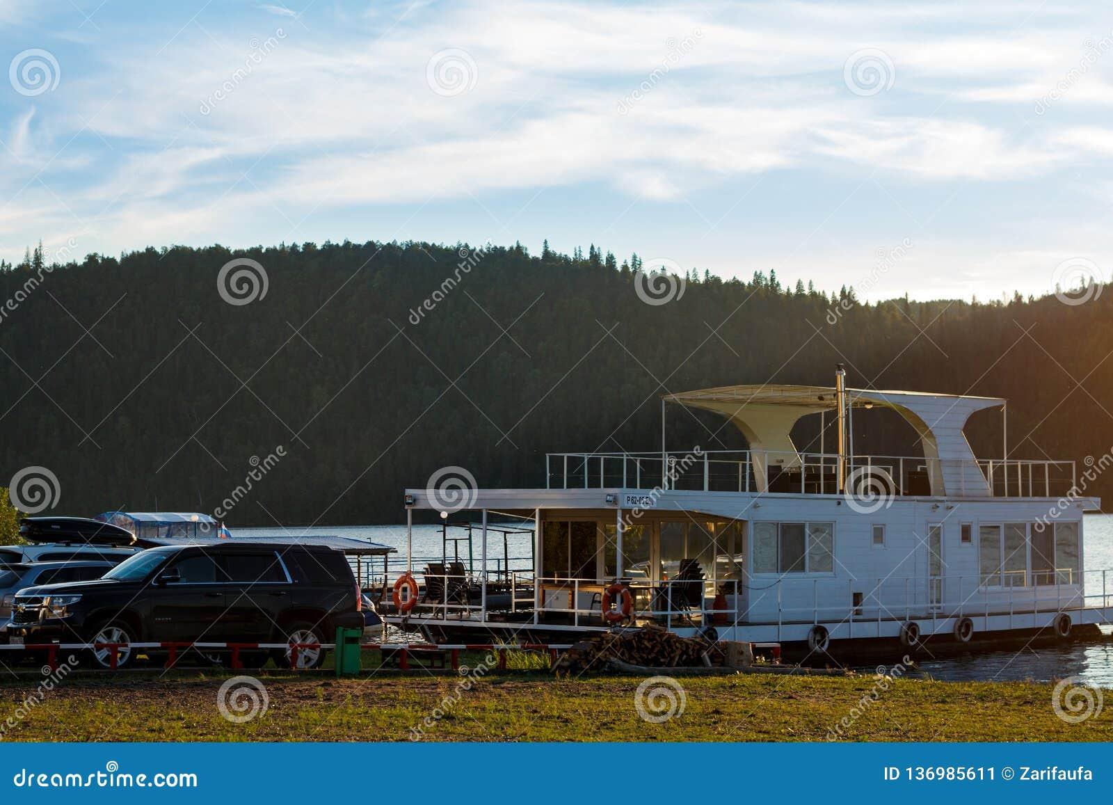 Pavlovsk-Reservoir, Russland - 10. August 2018: weißes Hausboot geparkt auf dem Ufer