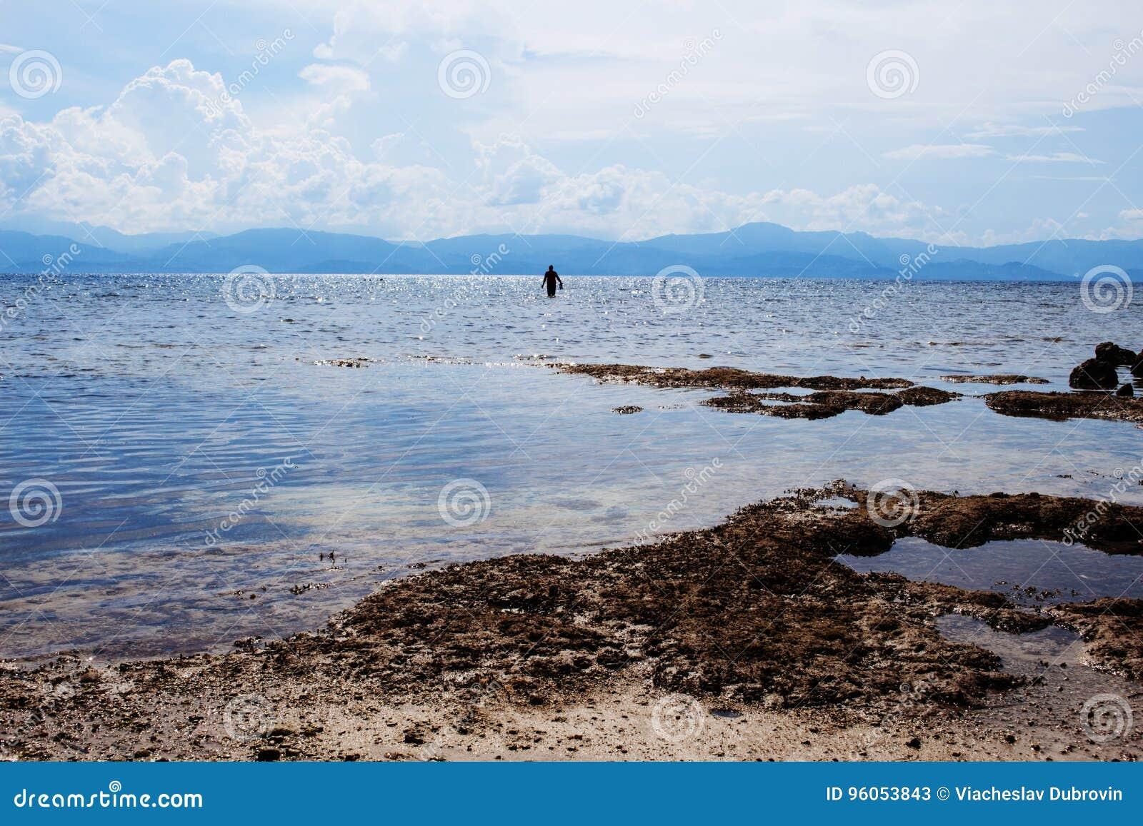 Paysage de mer avec la silhouette de l homme Paysage marin avec l île éloignée