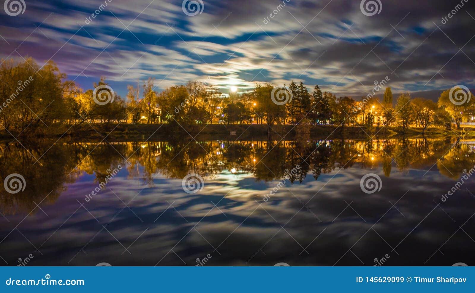Paysage de nuit au-dessus de rivière avec des arbres allumés par des lumières et des nuages de ville dans le mouvement