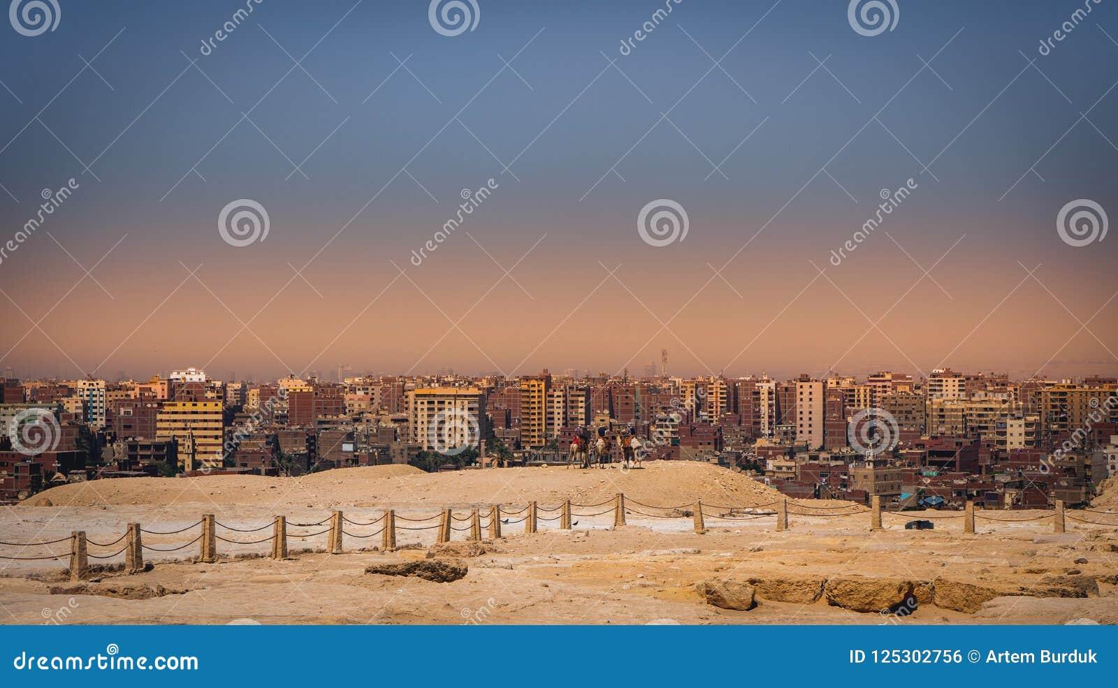 Paysage de ville de coucher du soleil Gizeh le Caire avec des pyramides de plateau