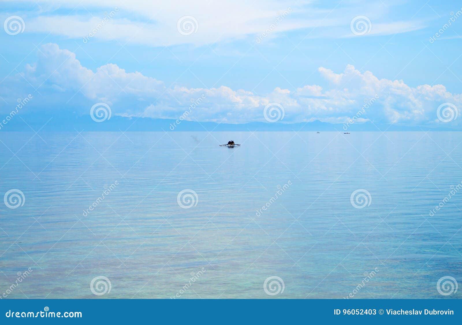 Paysage marin avec le bateau de pêcheur et le ciel bleu Vue de détente de mer avec l eau de mer immobile