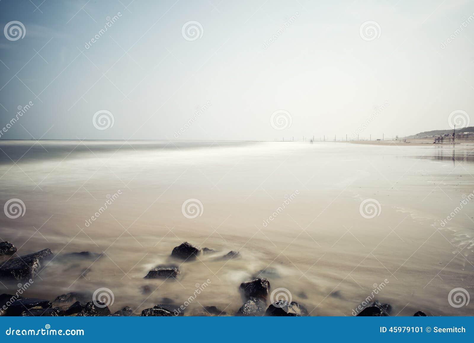 Paysage marin brumeux minimaliste avec des roches