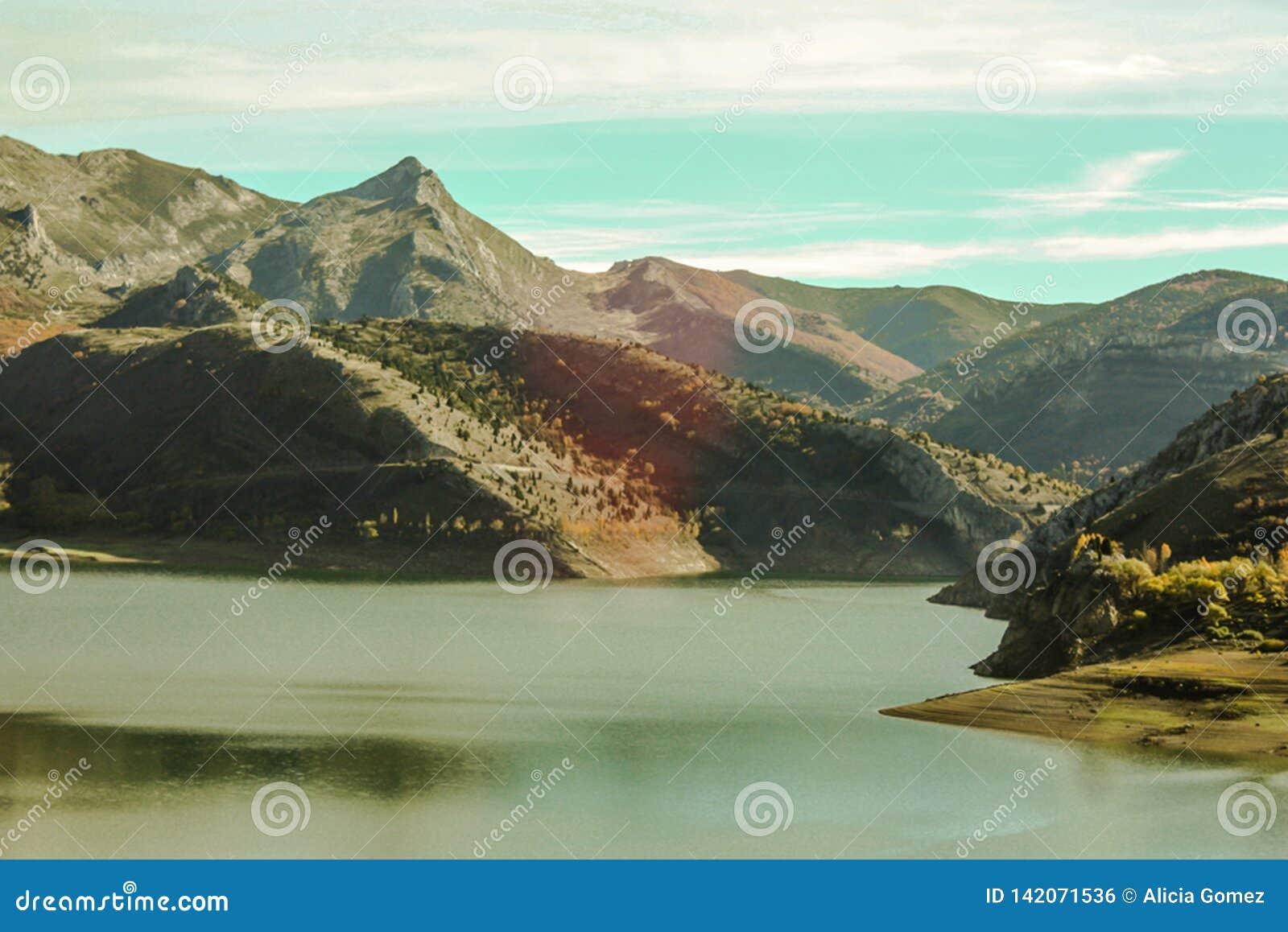 Paysage naturel montagneux avec le lac dans le premier plan, terre de différentes couleurs