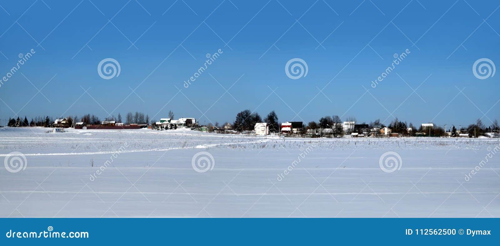 Paysage rural avec un village sur l horizon après champ de neige sous le ciel sans nuages bleu clair sur la vue panoramique lumin