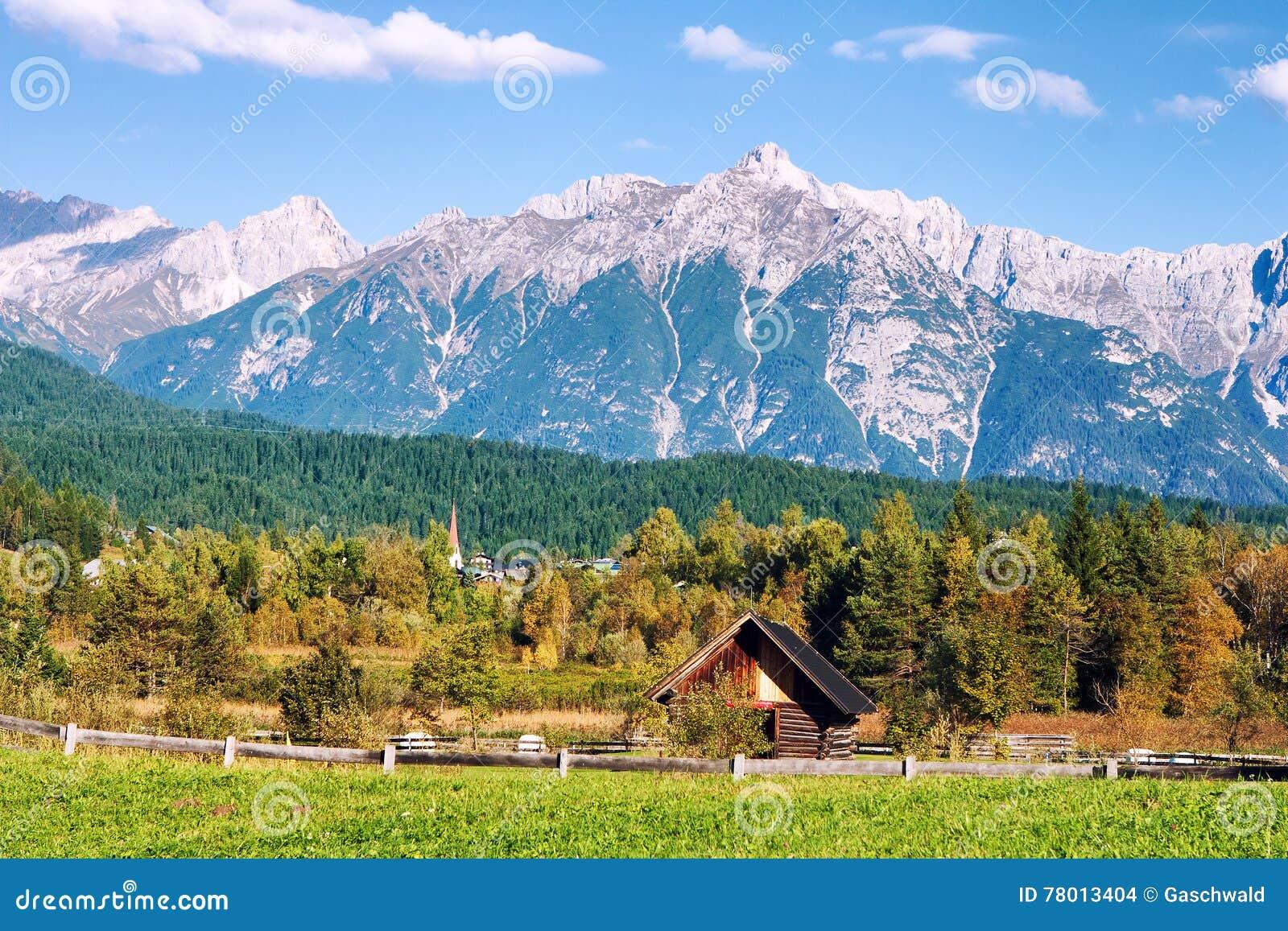 Paysage tyrolien idyllique avec les collines, la forêt, la maison de ferme et les champs verts