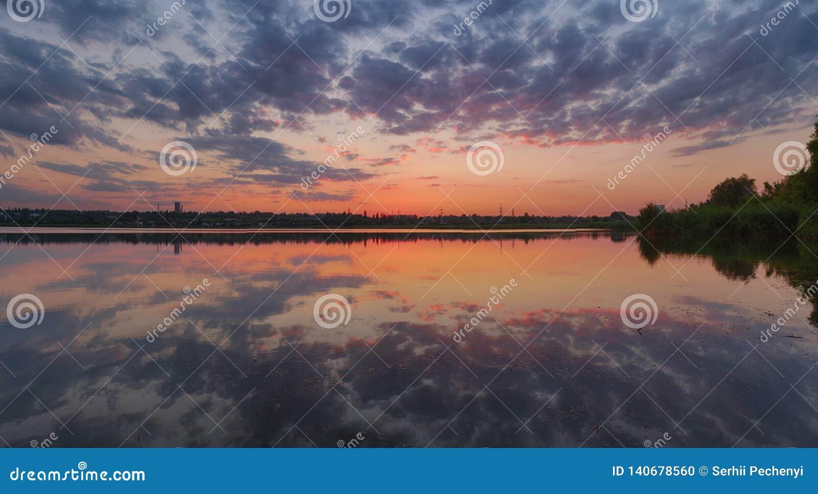 Paysage ukrainien de coucher du soleil d été avec le ciel nuageux reflété par l eau immobile