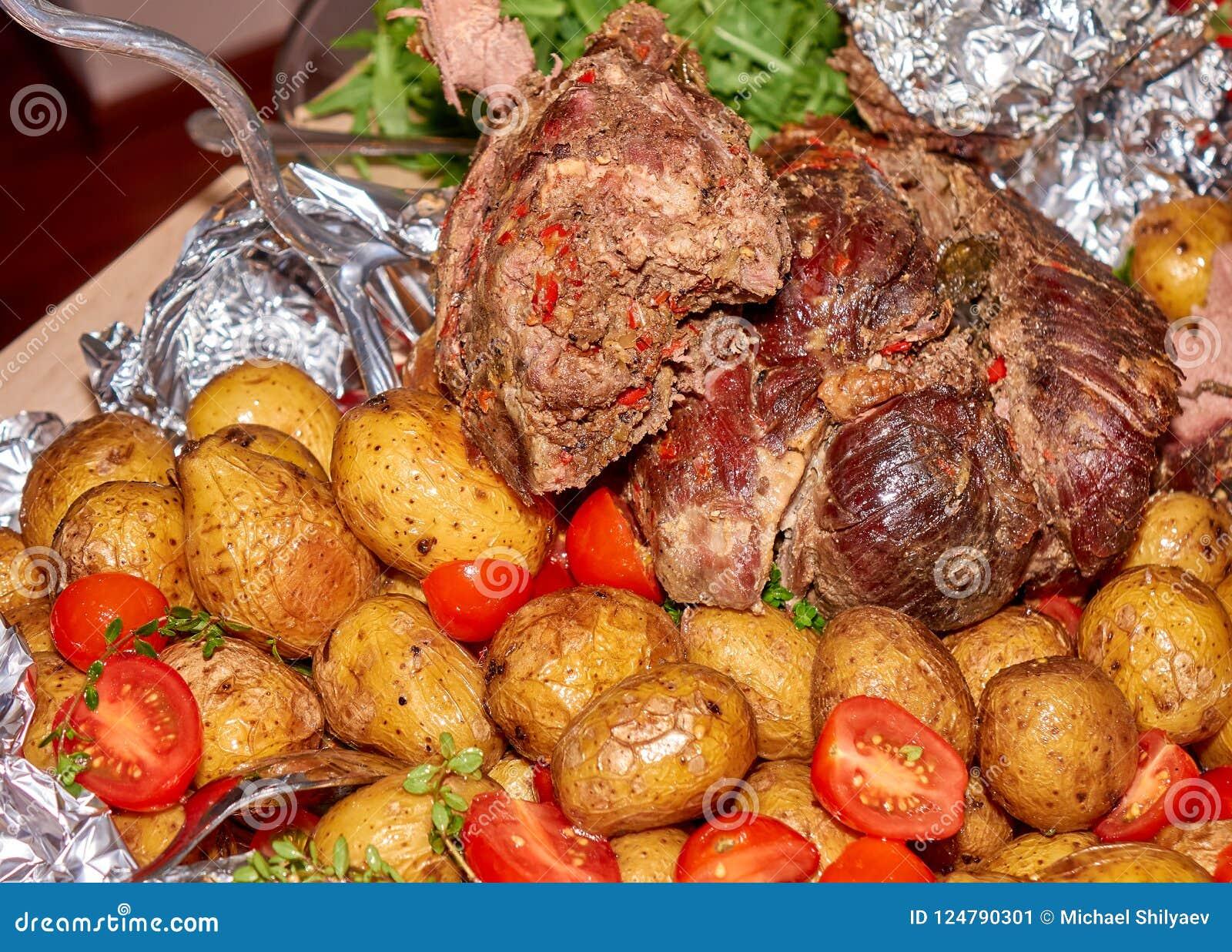 Paz grande da carne roasted da carne de carneiro com batatas cozidas e os tomates frescos