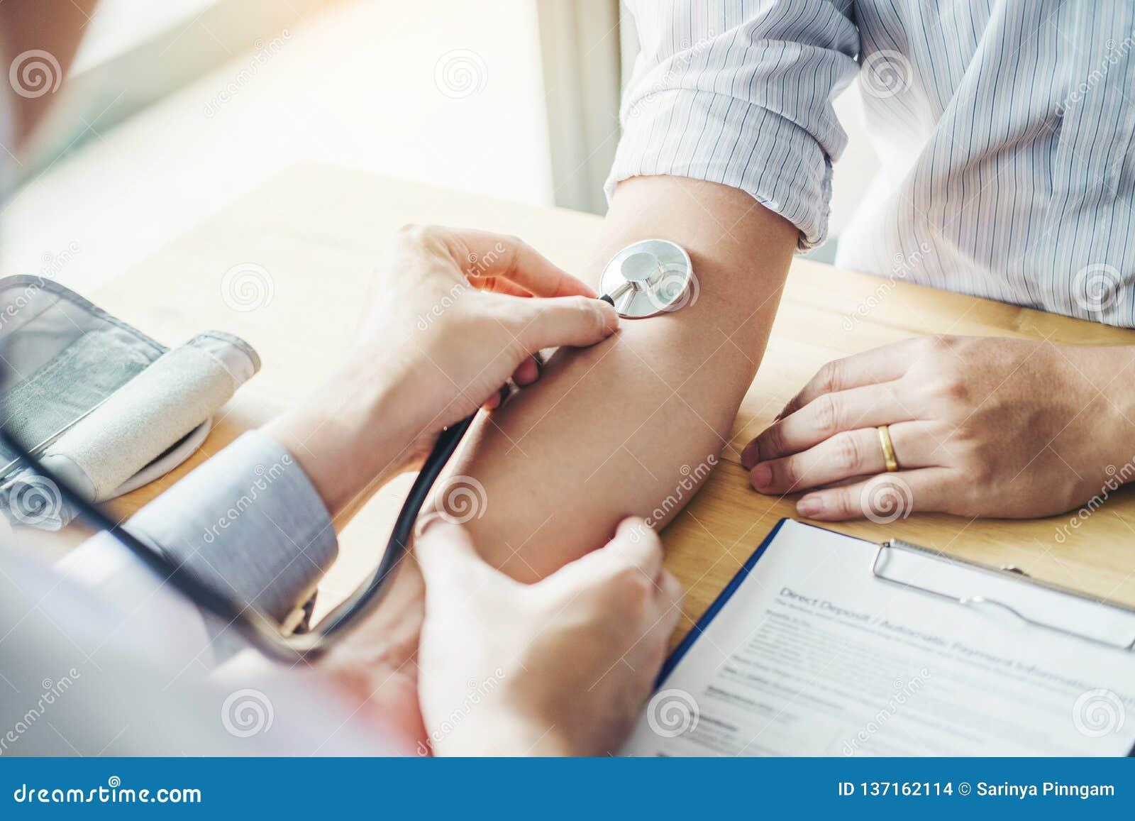 Paziente arterioso dell uomo di pressione sanguigna del dottore Measuring sulla sanità del braccio in ospedale